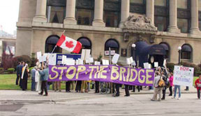 Community Air members demonstrating to stop the bridge in front of the Harbour Commissioner's building, the headquarters of the Toronto Port Authority.